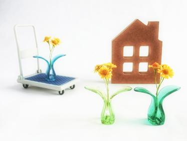 プラスチッククリップに挟んだ黄色い花とミニチュアの台車と家。花き取引、小売の概念。