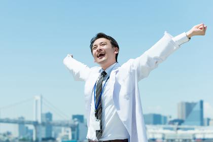 バンザイしてリラックスする医者
