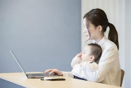 赤ちゃんを抱えてノートパソコンを操作する女性