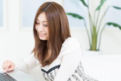 部屋でラップトップコンピューターを見る女性