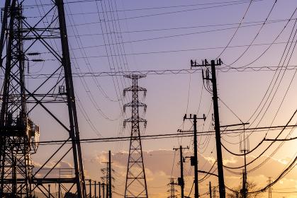 夕暮れの送電線と電柱のシルエット