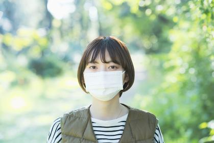 緑あふれる場所でマスクを着ける若い女性