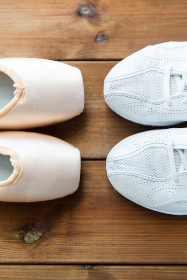 close up of sneakers and pointe shoes on wood