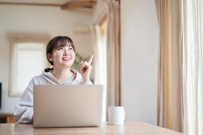 リビングで笑顔でパソコン操作をするアジア人女性