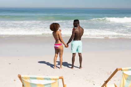 A mixed race couple enjoying free time on beach on a sunny day together, drinking cocktails, holding hands, having fun with sun shining on their faces.