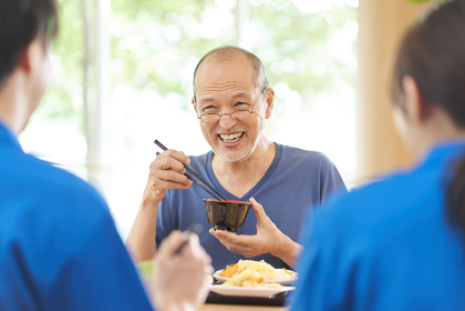介護施設で楽しく食事をする高齢者