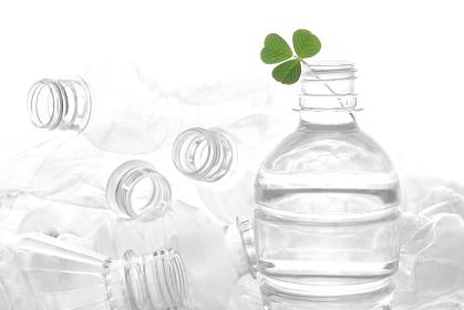 透明な背景に積み重なったペットボトルに入れた緑の葉っぱ