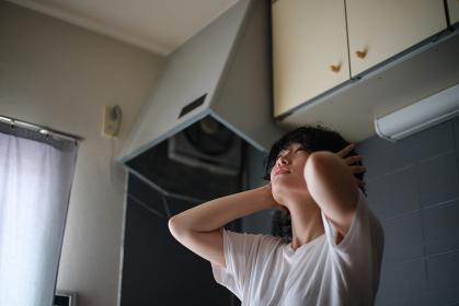 上の階の騒音に悩む女性