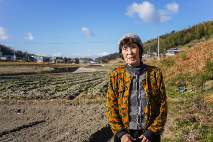 田舎でほほえむ高齢の女性