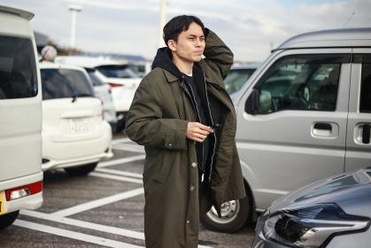 駐車場で車を探す男性