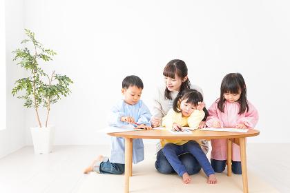 お絵かきをする子どもたちと保育士