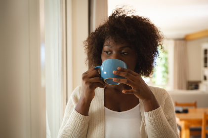 Thoughtful african american woman standing in dining room drinking cup of coffee. spending free time at home.