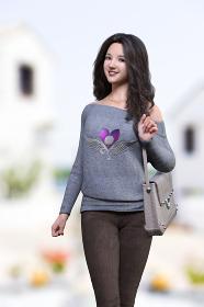 ハートマークのトップスを着用した笑顔の黒髪の女性が肩らかバッグを下げて街中を歩いている