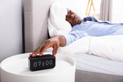 Man Sleeping On Bed Turning Off Clock