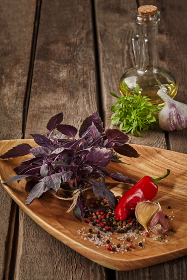 Purple basil with spices and olive oil on wooden table