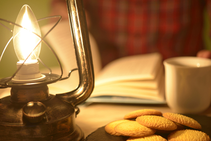 ランタンの灯りで読書をする日本人シニア