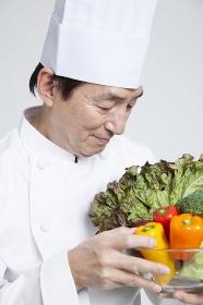 野菜を持って微笑む調理師