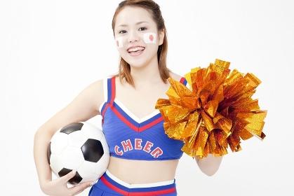 サッカーボールを持って微笑むチアガール