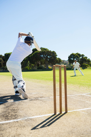 Rear view of cricket player batting while playing on field