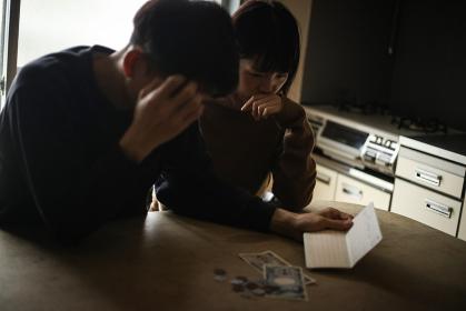 通帳を見て悩む夫婦
