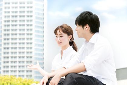 屋外で会話をする若い男女