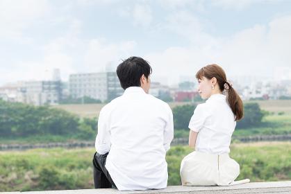 景色が綺麗な屋外で座って会話するカップル
