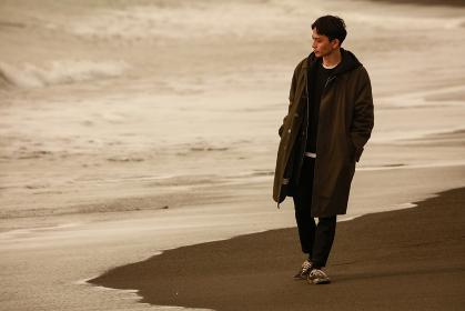 海岸を一人で歩く男性