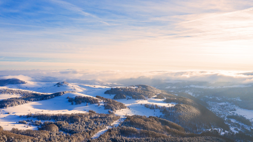 Aerial view of a gold sunset over winter snow.