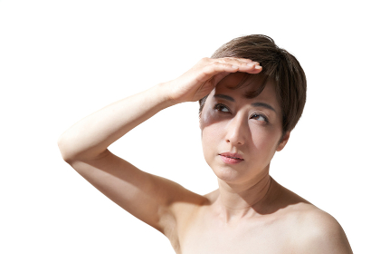 強い日差しを避ける中年の日本人女性