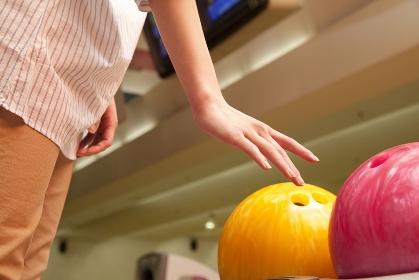 ボウリング球を持とうとする女性の手元