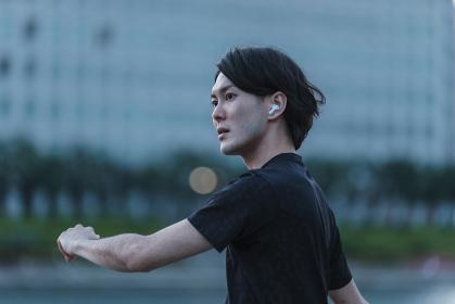 音楽を聞きながらジョギングの準備をする若い男性