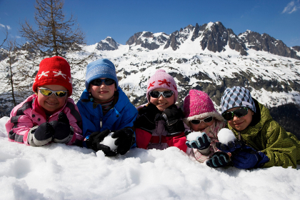 5 kids lying in the snow.