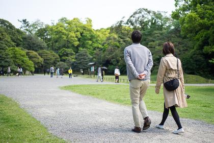 爽やかな緑の公園を散歩する夫婦