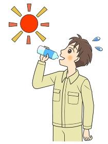 屋外で水分補給する作業着の若い男性