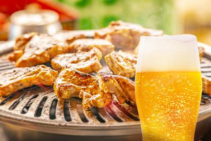 焼肉の背景と泡が垂れた水滴のついたグラスビールの画像