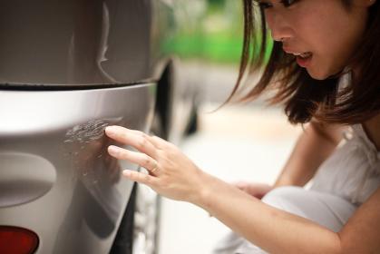 車の傷を確認する女性