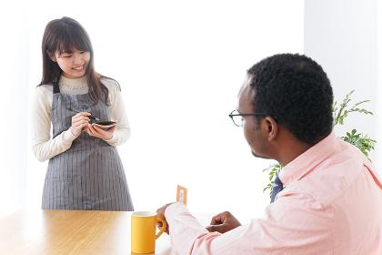 外国人に接客をするカフェスタッフ