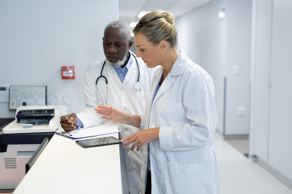 Diverse male and female doctors standing in hospital corridor looking at medical chart document. medicine, health and healthcare services.