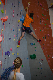 Woman with rope looking at man climbing wall in health club