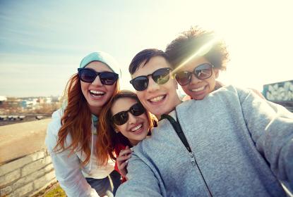 group of happy friends taking selfie on street