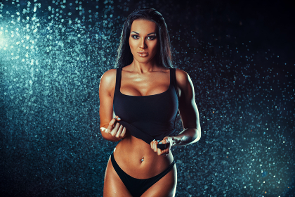 Young sexy brunette woman fashion portrait with rain effect. Tattoo on right hand.