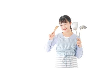 笑顔で料理をする若い主婦