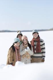 雪原で雪だるまを持ち微笑む若者たち