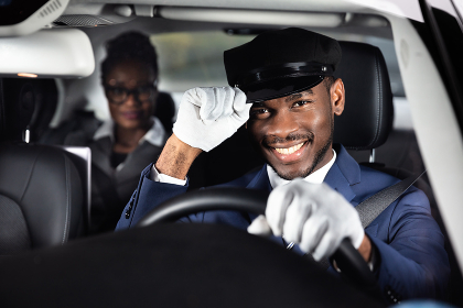 Portrait Of A Smiling Male Chauffeur Driving Car