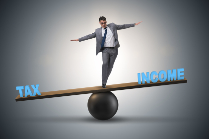 Businessman balancing between income and tax in business concept