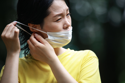 マスクを着け耳が痛む女性