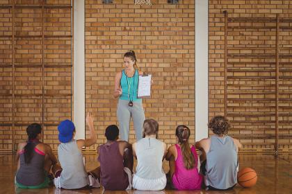 Female coach mentoring high school kids