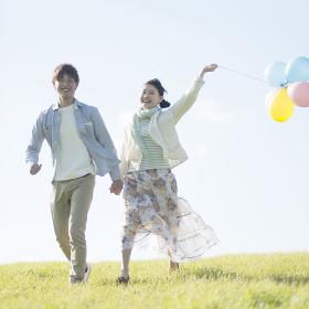 風船を持ち草原を走るカップル