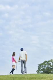 ゴルフ場で歩く日本人カップル