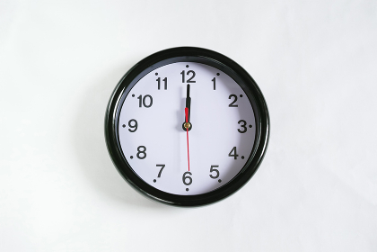 白い壁に掛かった12時の時計